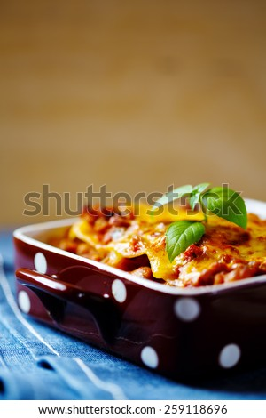 Italian Food. Hot tasty Lasagna plate served with fresh basil leaf. Selective focus. - stock photo