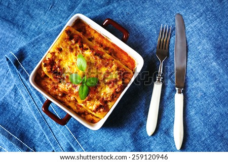 Italian Food. Hot tasty Lasagna plate served with fresh basil leaf. Top view, selective focus. - stock photo