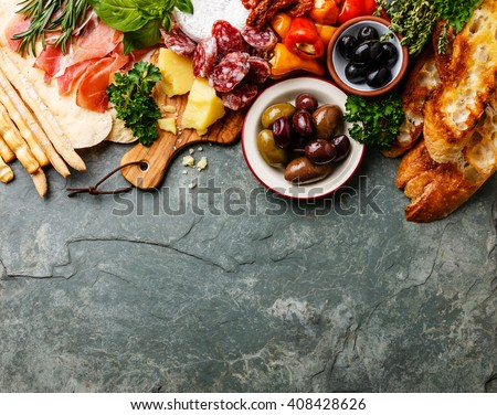 Italian food ingredients background with ham, salami, parmesan, olives, bread sticks - stock photo