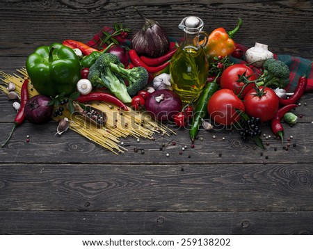 Italian food ingredients: pasta, tomatoes, mushrooms, herbs, vegetables, nuts and spices on wooden background