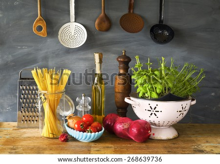 italian food ingredients, spaghetti,tomatoes, herbs, kitchen utensils - stock photo