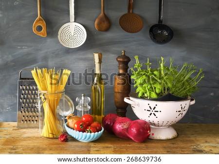 italian food ingredients, spaghetti,tomatoes, herbs, kitchen utensils - stock photo