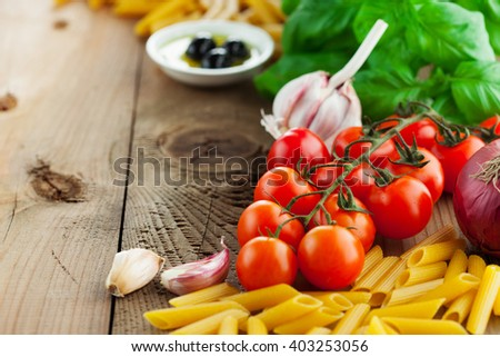 Italian food ingredients - tomatoes, basil, olives, olive oil, garlic, peppercorns and penne on rustic wooden background, selective focus - stock photo