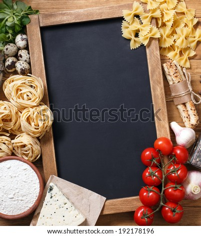 Italian food on vintage wood background, with chalkboard, with copyspace - stock photo