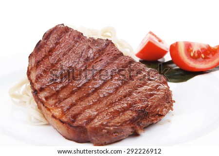 italian food : pasta with tomato on basil and roasted sirloin beef  steak on plate isolated over white background - stock photo