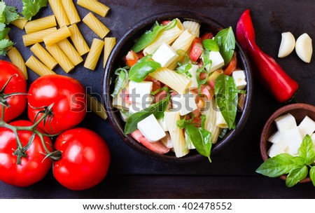 Italian food. Salad with pasta, vegetables and cheese or tofu and ingredients - tomatoes, dry pasta, chili, basil, garlic, cheese on dark background. Top view - stock photo