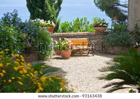 Italian garden with a bench, sea as background - stock photo