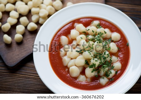 Italian gnocchi served with tomato sauce and parsley, closeup - stock photo