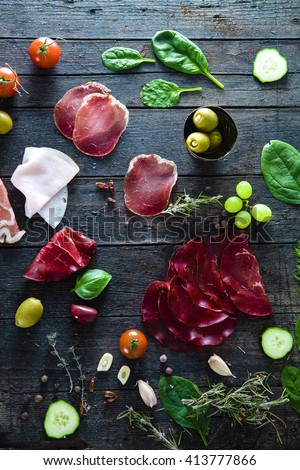 Italian ham, prosciutto and salami. Ingredients for bruschetta, crostini or sandwich bar. Rustic top view of ingredients. Ham with vegetables and spices