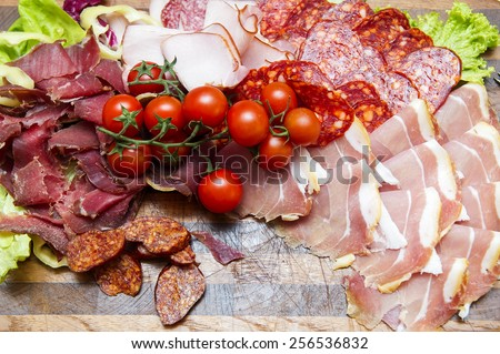 Italian ham prosciutto and salami with cherry tomatoes at the background - stock photo