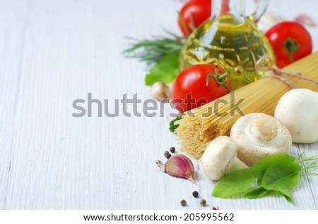 Italian ingredients - pasta, tomatoes, mushrooms, herbs, olive oil - on a white wooden background. - stock photo