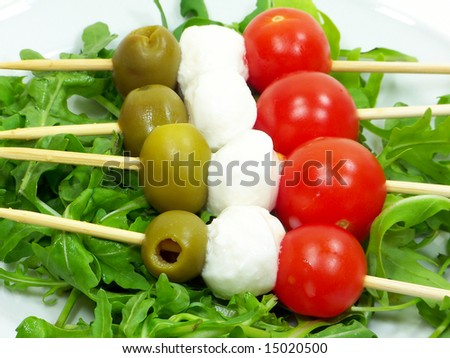 Italian kebabs with mozzarella cheese olives and tomatoes over rocket bed - stock photo