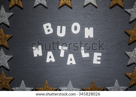 Italian language Christmas wish, white letter text on dark slate background with golden and silver star frame. - stock photo