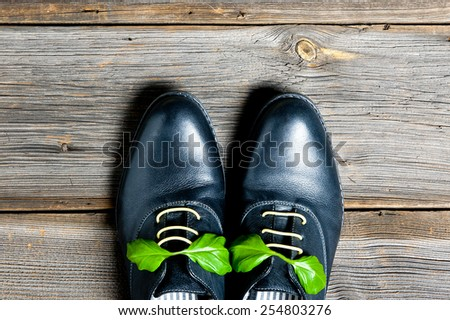italian leather shoes concept: boots laced with spaghetti and basil leaf as bow - stock photo
