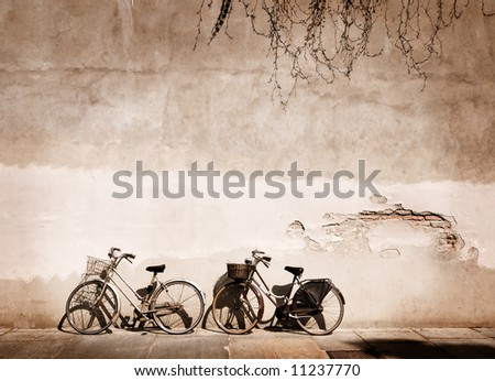 Italian old-style bicycles leaning against a wall in the historic centre of Parma - stock photo