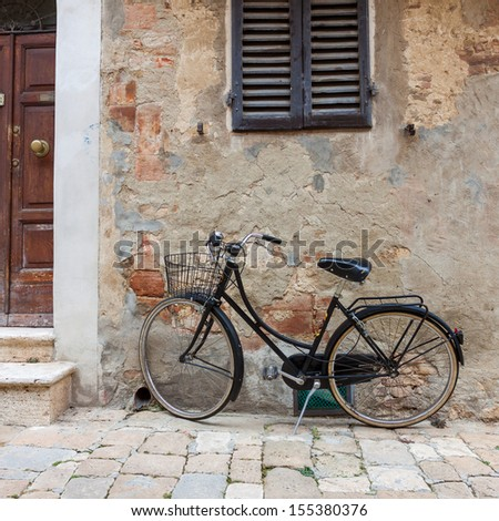 Italian old-style bicycles leaning against a wall in the historic centreof Ferrara - stock photo