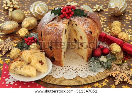 Italian panettone christmas cake and slice with red and gold bauble decorations, holly and winter flora over oak background with stars. - stock photo