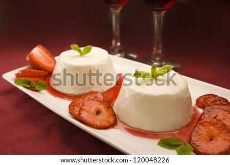 Italian panna cotta dessert garnished with fresh mint, strawberries and syrup - stock photo