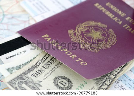 Italian passport, us dollars and airline ticket on a road map - stock photo