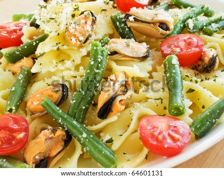 Italian pasta farfalle with mussels and vegetables. Shallow dof. - stock photo
