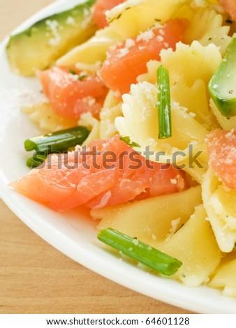 Italian pasta farfalle with smoked salmon and avocado. Shallow dof. - stock photo
