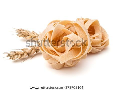 Italian pasta fettuccine nest and wheat ears still life isolated on white background - stock photo