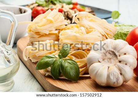 Italian pasta fettuccine nest on cutting board - stock photo