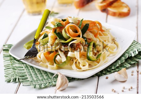 Italian pasta noodles with assorted vegetables in square dish - stock photo