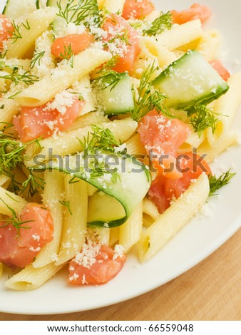 Italian pasta penne with smoked salmon and cucumber. Shallow dof. - stock photo