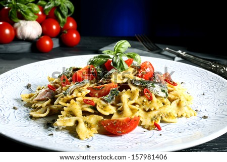 italian pasta with anchovies and tomatoes dark background - stock photo