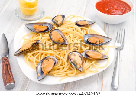 Italian pasta with Galician mussels in white wood - stock photo