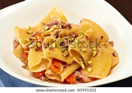 italian pasta with pistachio nuts an cherry tomato - stock photo