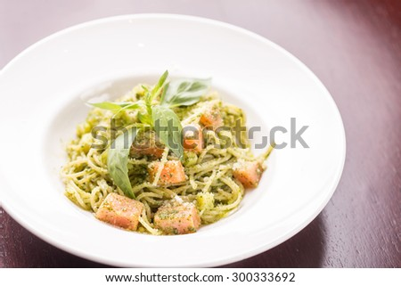 Italian pasta with salmon and basil on wooden table at restaurant - stock photo