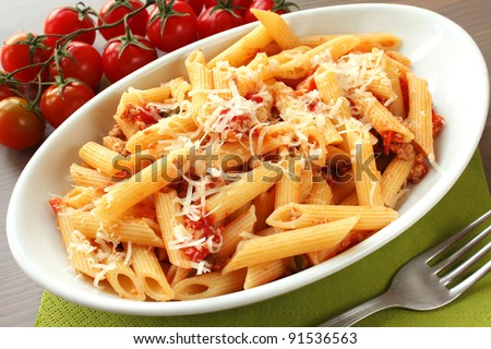 Italian pasta with sauce and parmesan cheese, served on a white oval plate - stock photo