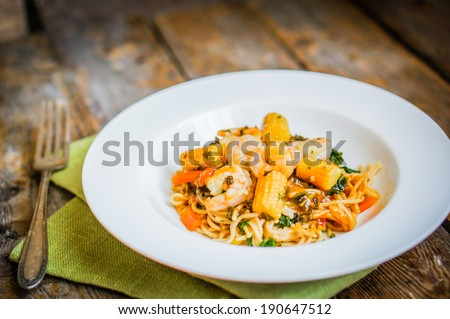 Italian pasta with shrimps and vegetables on wooden background - stock photo