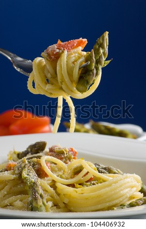 Italian pasta with tomatoes and asparagus. - stock photo