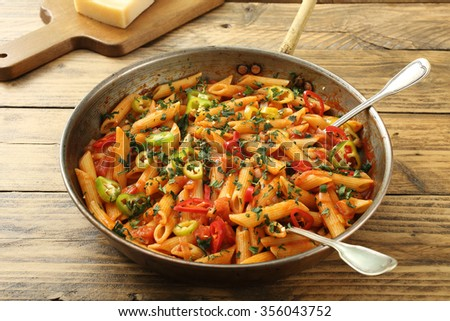 italian pasta with vegetables in sauce tomato rustic table background - stock photo