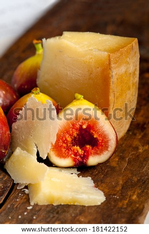 italian pecorino cheese and fresh figs macro closeup over old wood boards