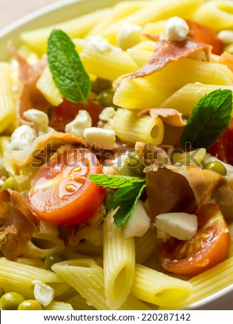 Italian Penne Pasta Salad With Mozzarella, Tomatoes And Prosciutto Ham - stock photo
