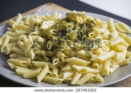 Italian penne pasta with green pesto sauce on a dark blue background.