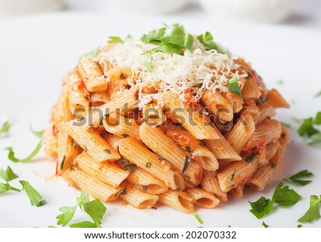 Italian penne rigate pasta with tomato sauce, grated parmesan cheese and parsley - stock photo