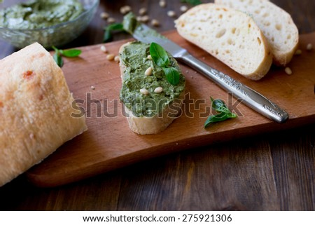 italian pesto preparation vegan without parmesan with black olives ingredients on table basil, garlic, lemon, pine nuts, fresh and organic on dark wood rustic table backgroundpesto on a ciabatta bread - stock photo