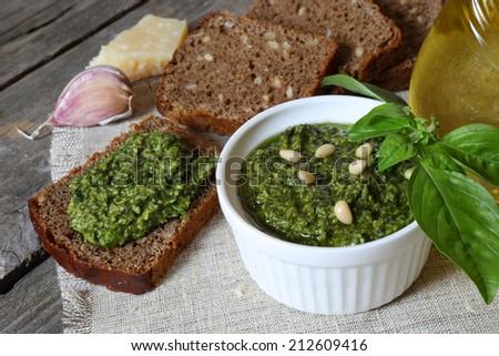 Italian pesto sauce and rye toast on a wooden table - stock photo
