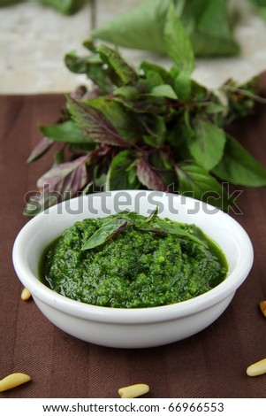 Italian pesto sauce on a wooden board with basil - stock photo