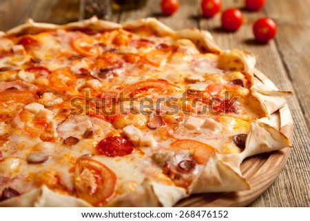 "Italian pizza ""Bavarian"" on wooden table. Nearby are containers with spices and olive oil. Near them are cherry tomatoes. The pizza is cut into six parts. Has not the traditional form of the edges. - stock photo"
