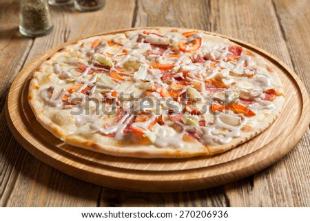 "Italian pizza ""Caesar"" lies on wooden table.  - stock photo"