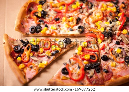 Italian Pizza closeup with a cut slice. Pizza with ham, pepperoni, olives,  corn and peppers