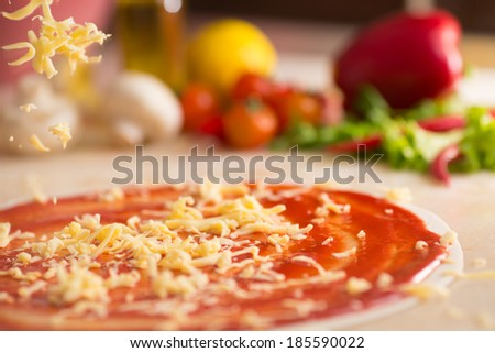 Italian pizza preparation with cheese falling. - stock photo