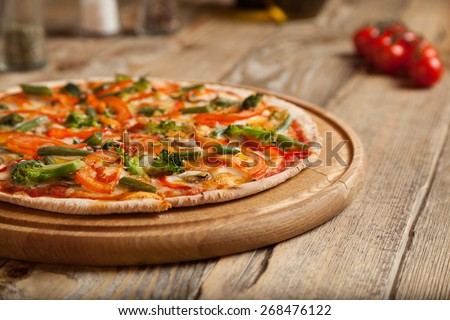 "Italian pizza ""Vegeterin"" on wooden table. On top of the pizza are baked sliced tomatoes, and asparagus boccoli. Nearby are containers with spices and olive oil. Near them are cherry tomatoes. - stock photo"