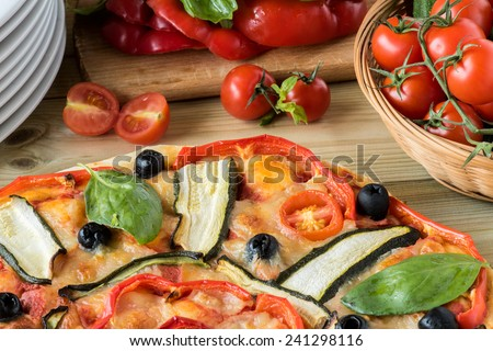 italian pizza with black olives, cherry tomatoes, eggplants and peppers on woodenboard - stock photo